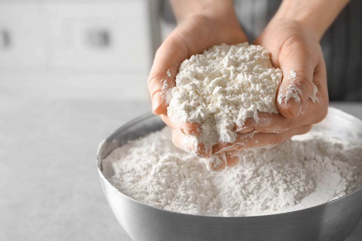 White flour in a silver bowl with hands scooping it up.