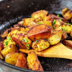 Wooden spatula removing fried potatoes out of iron skillet.