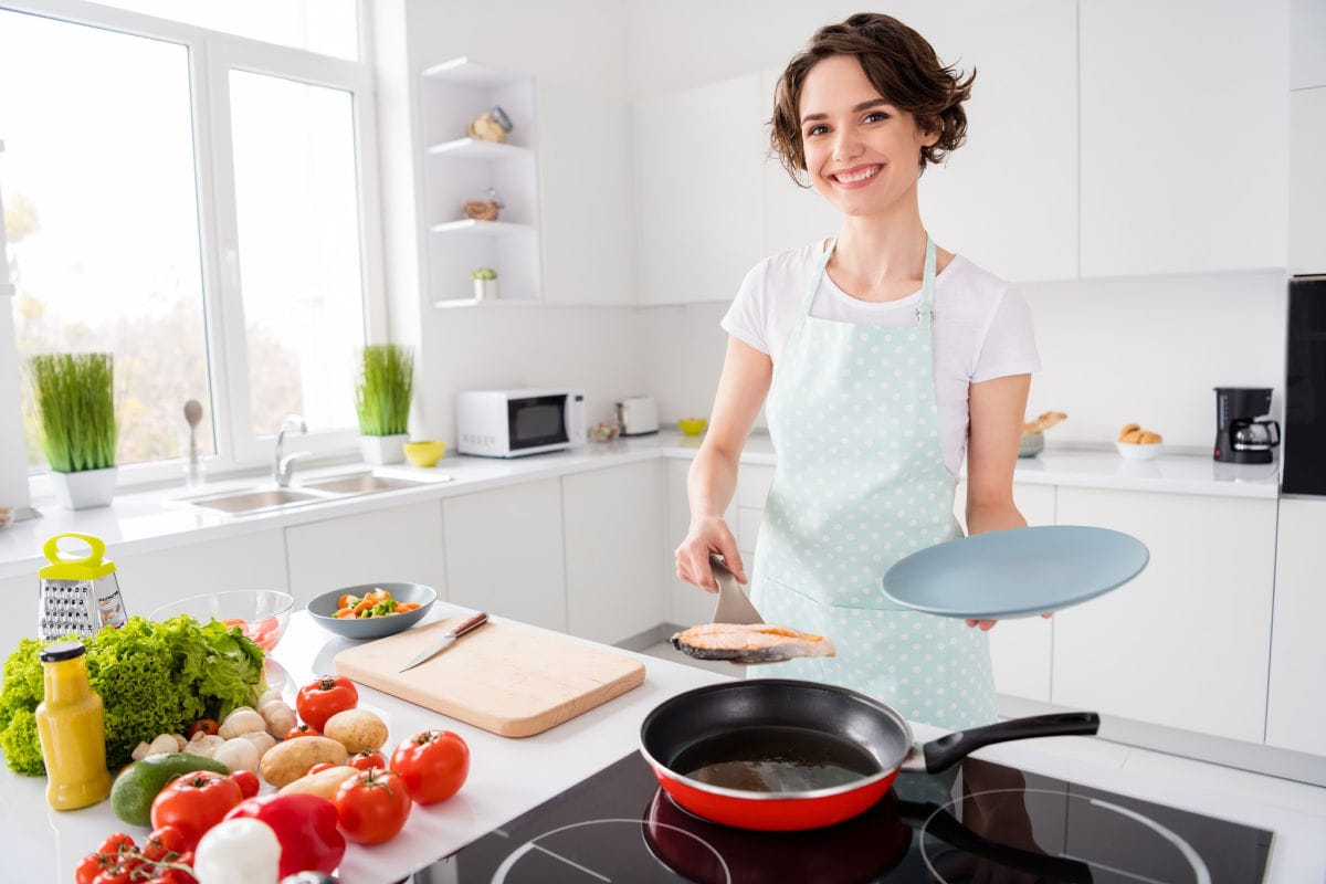 Smiling woman organizing her kitchen for cooking.