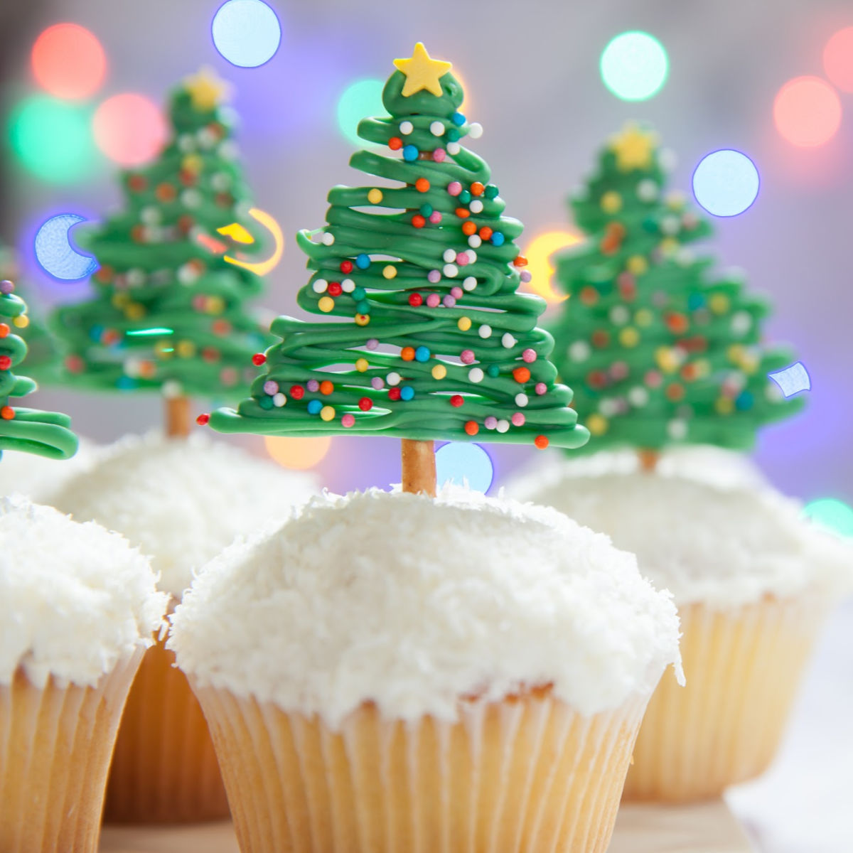 White cupcakes with edible Christmas tree decor on top.