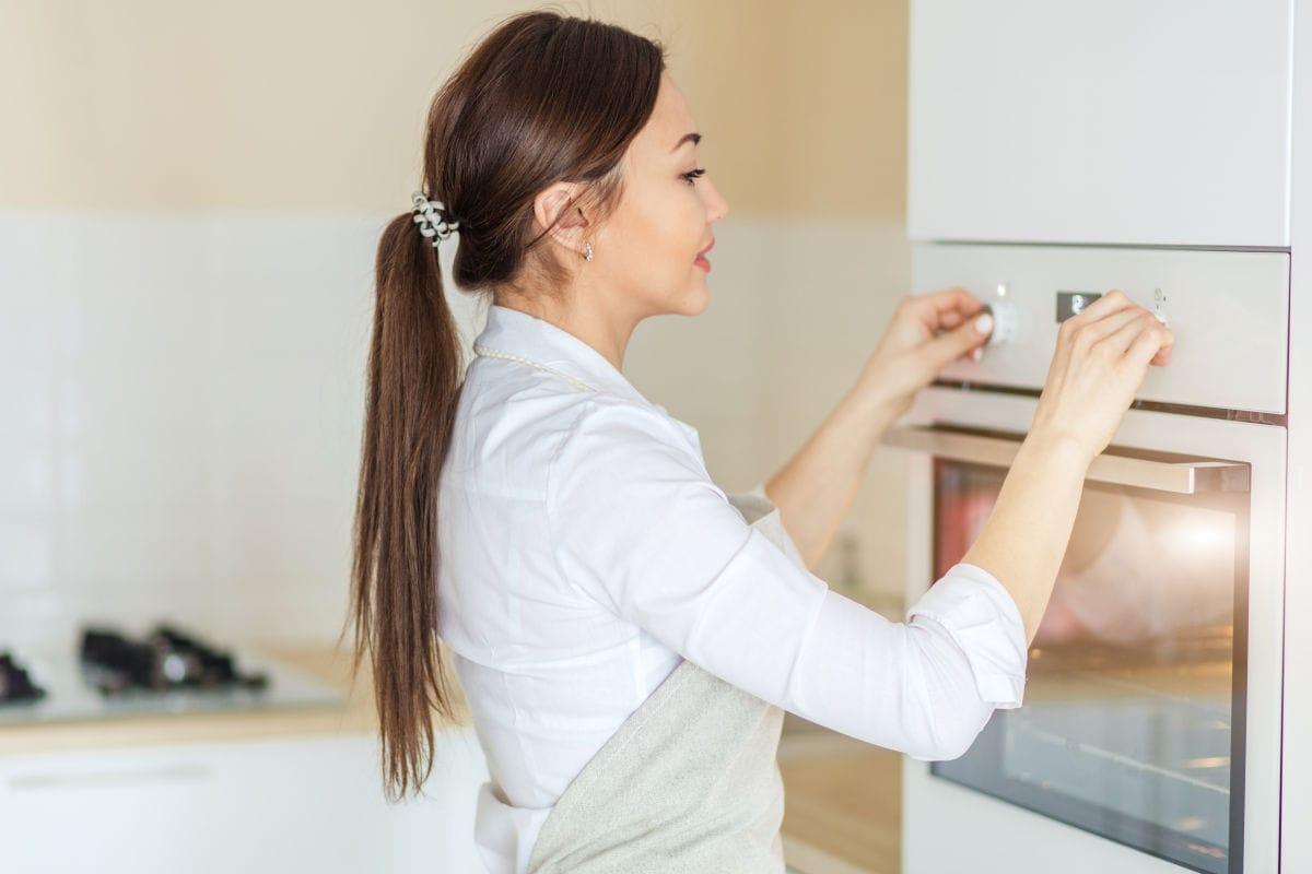 Girl preheating the oven.