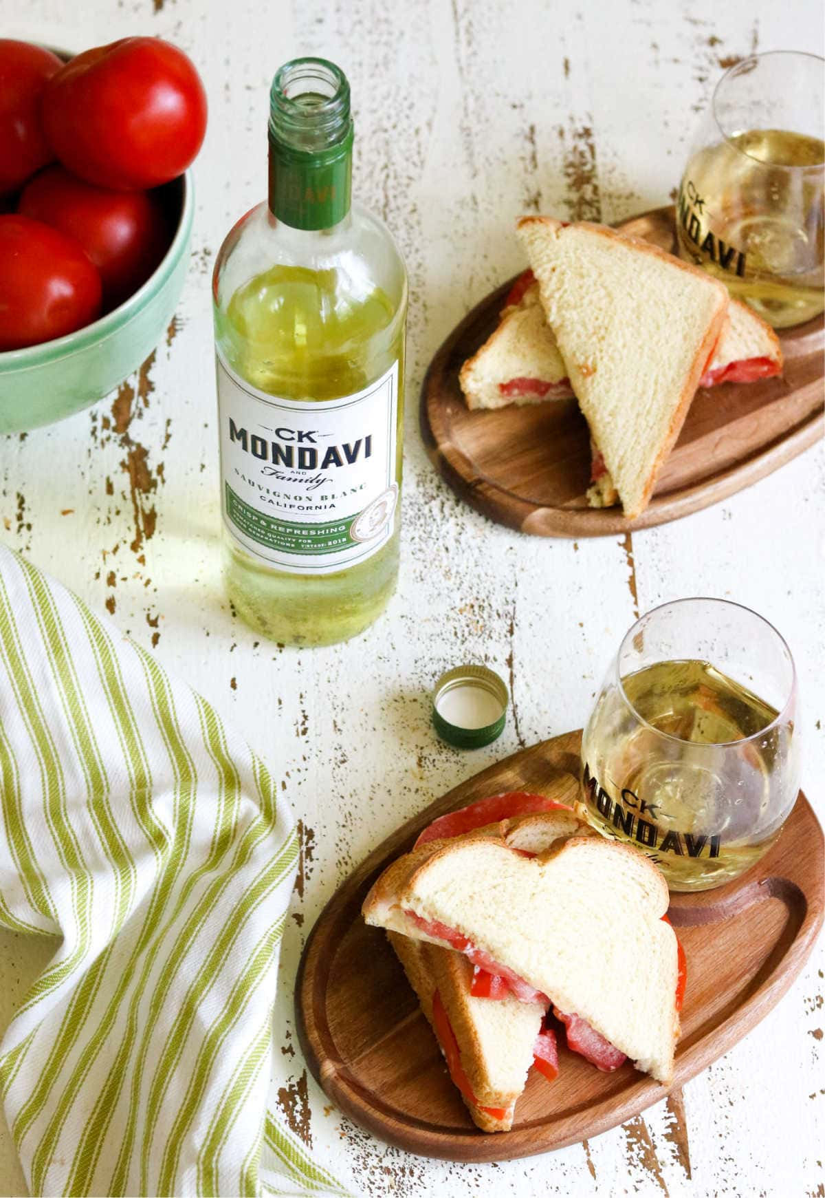 Plate of tomato sandwiches with a bottle of white wine.