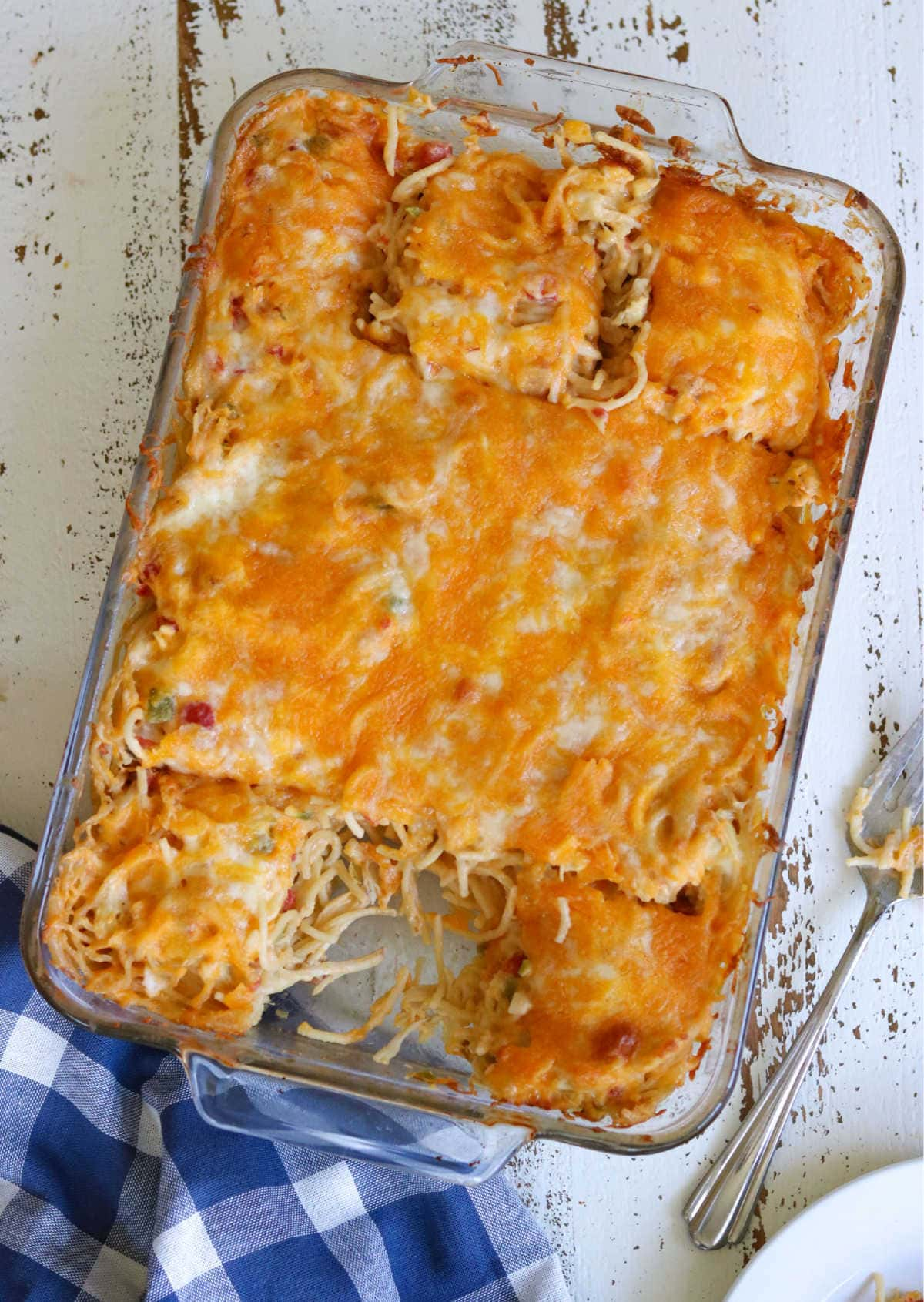 A baking dish with finished chicken spaghetti in itshowing the top of the casserole - one serving is removed.