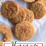 Chewy snickerdoodles on a piece of parchment paper with title text overlay for Pinterest.