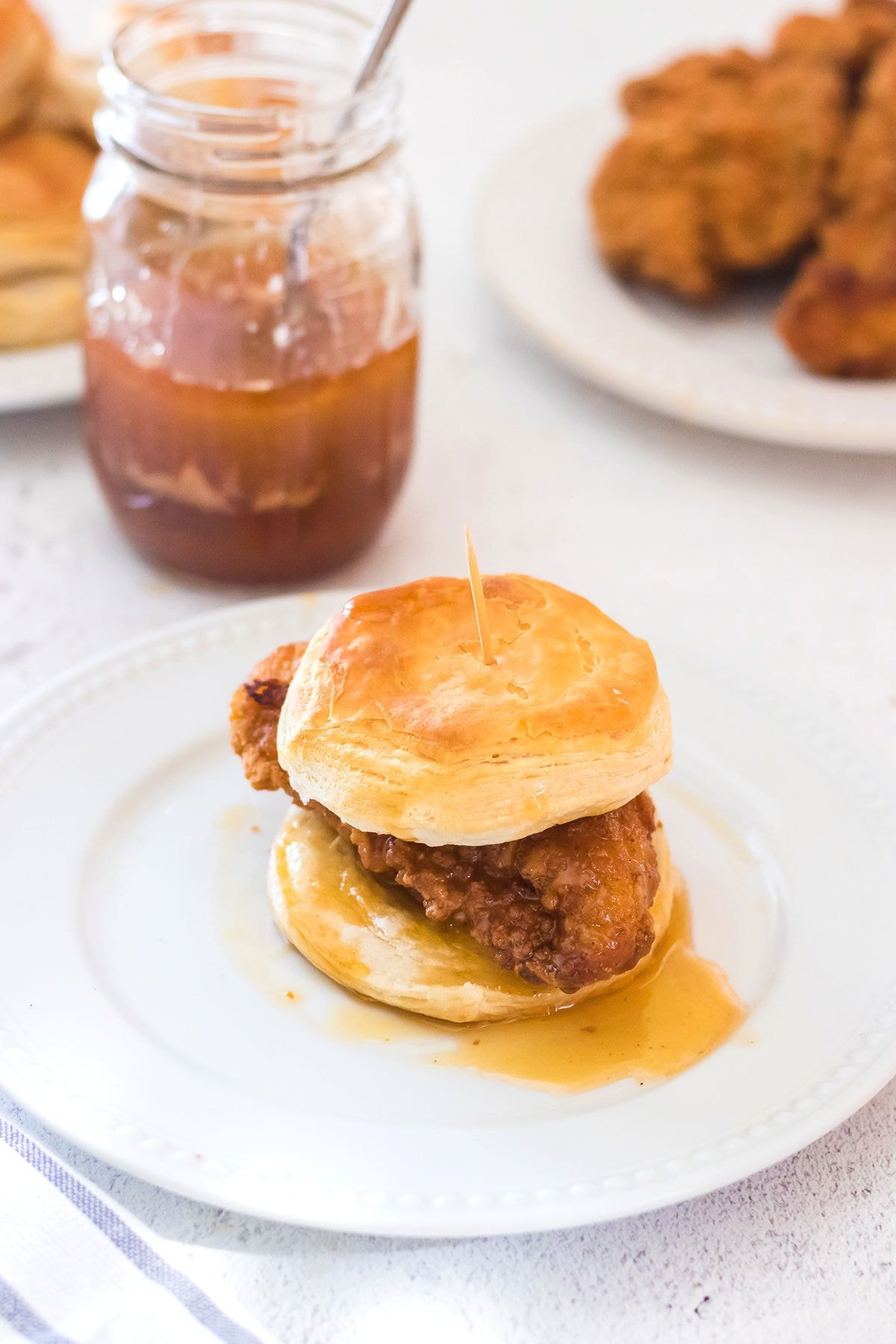 Finished chicken biscuit on a plate with ingredients in the background.