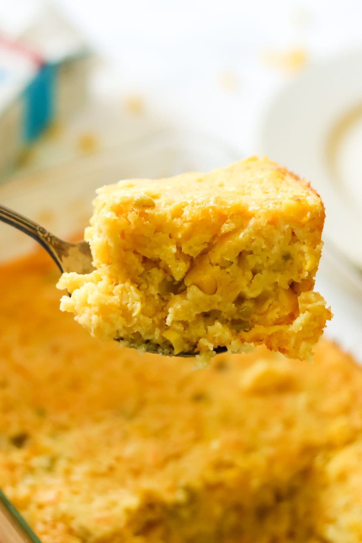 A serving of creamy corn casserole is lifted from the dish.