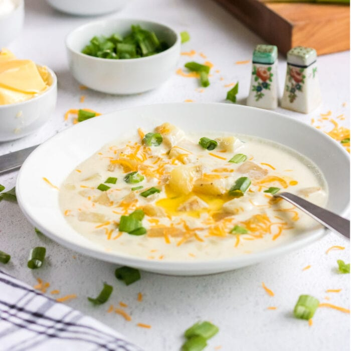 A closeup of potato soup in a white bowl garnished with butter.