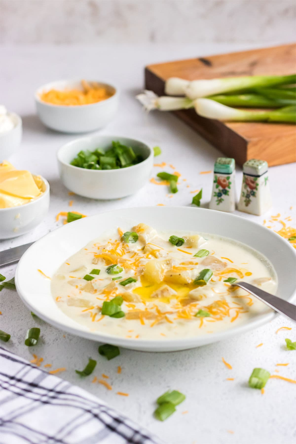 A bowl of creamy soup garnished with cheese and green onion.