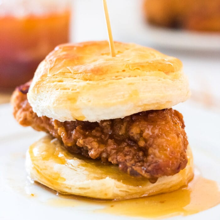 Close up of a biscuit with fried chicken on it and melted honey butter dripping from it.