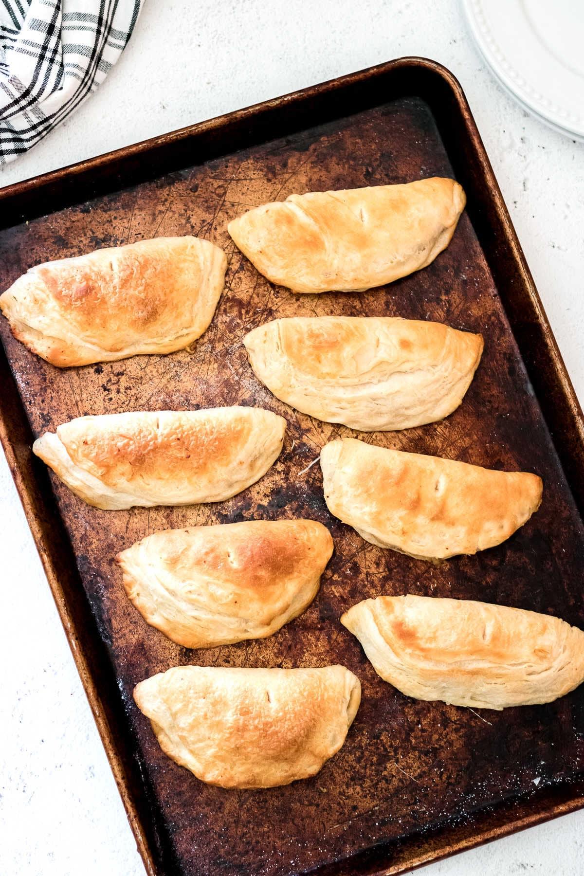 Finished empanadas on a baking sheet.