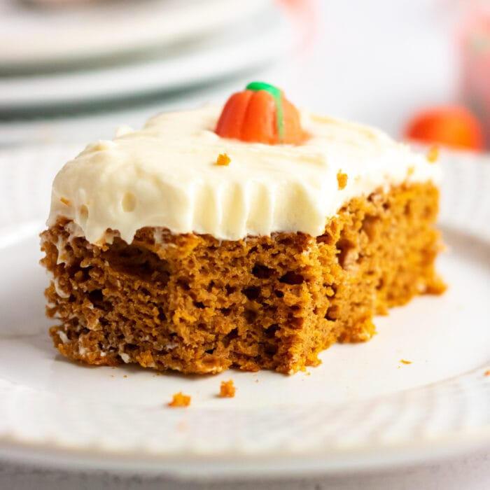 A serving of pumpkin cake with a bite taken out of it.