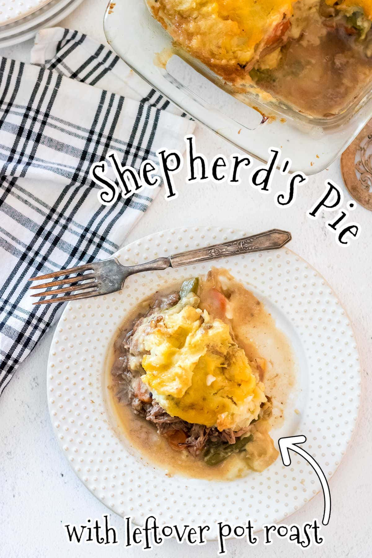 Overhead view of the finished casserole dish with a serving of the shepherd's pie on a nearby plate. Title text overlay.