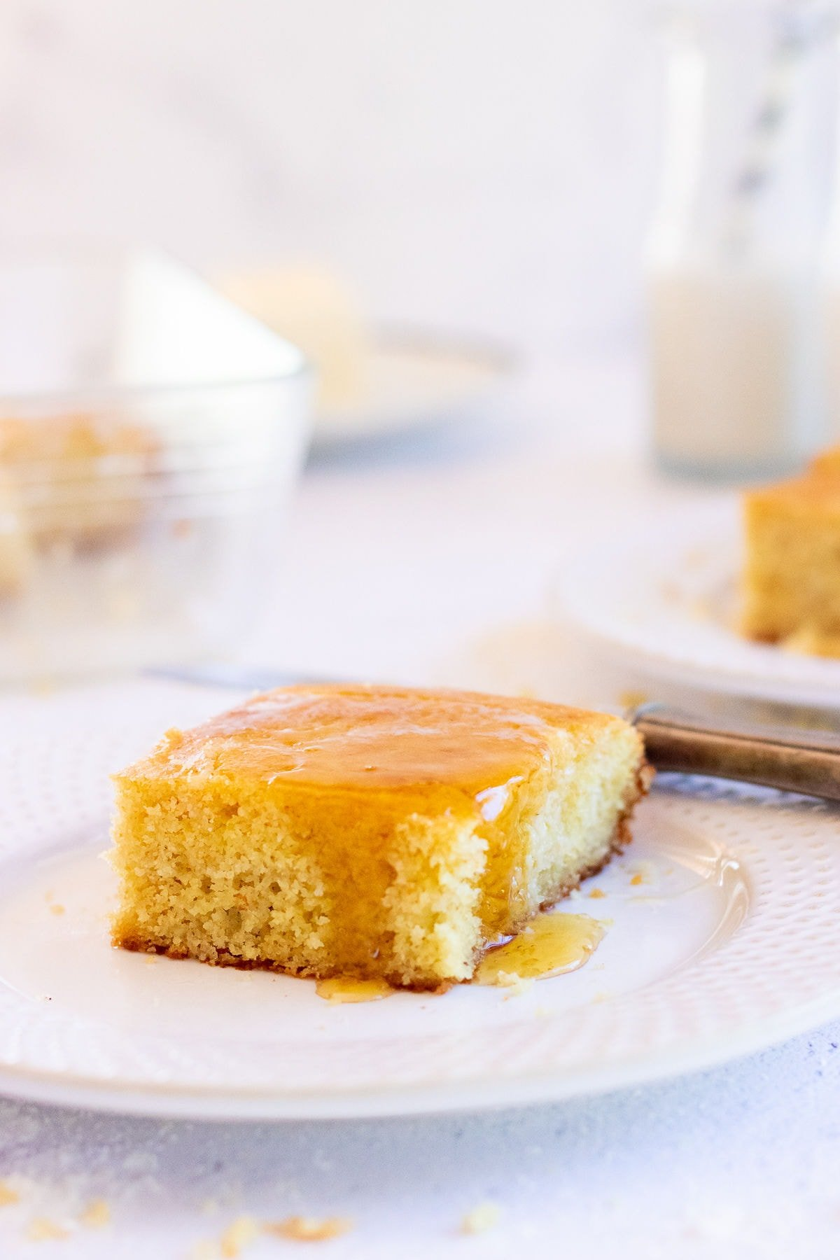 Square of buttermilk cornbread with honey dripping down the sides.