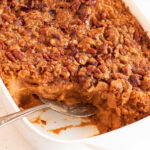 Close up of sweet potato crunch casserole with a serving removed from dish.