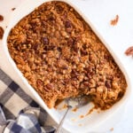 A sweet potato casserole with a serving removed.