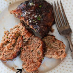Sliced meatloaf on plate with text overlay for Pinterest.