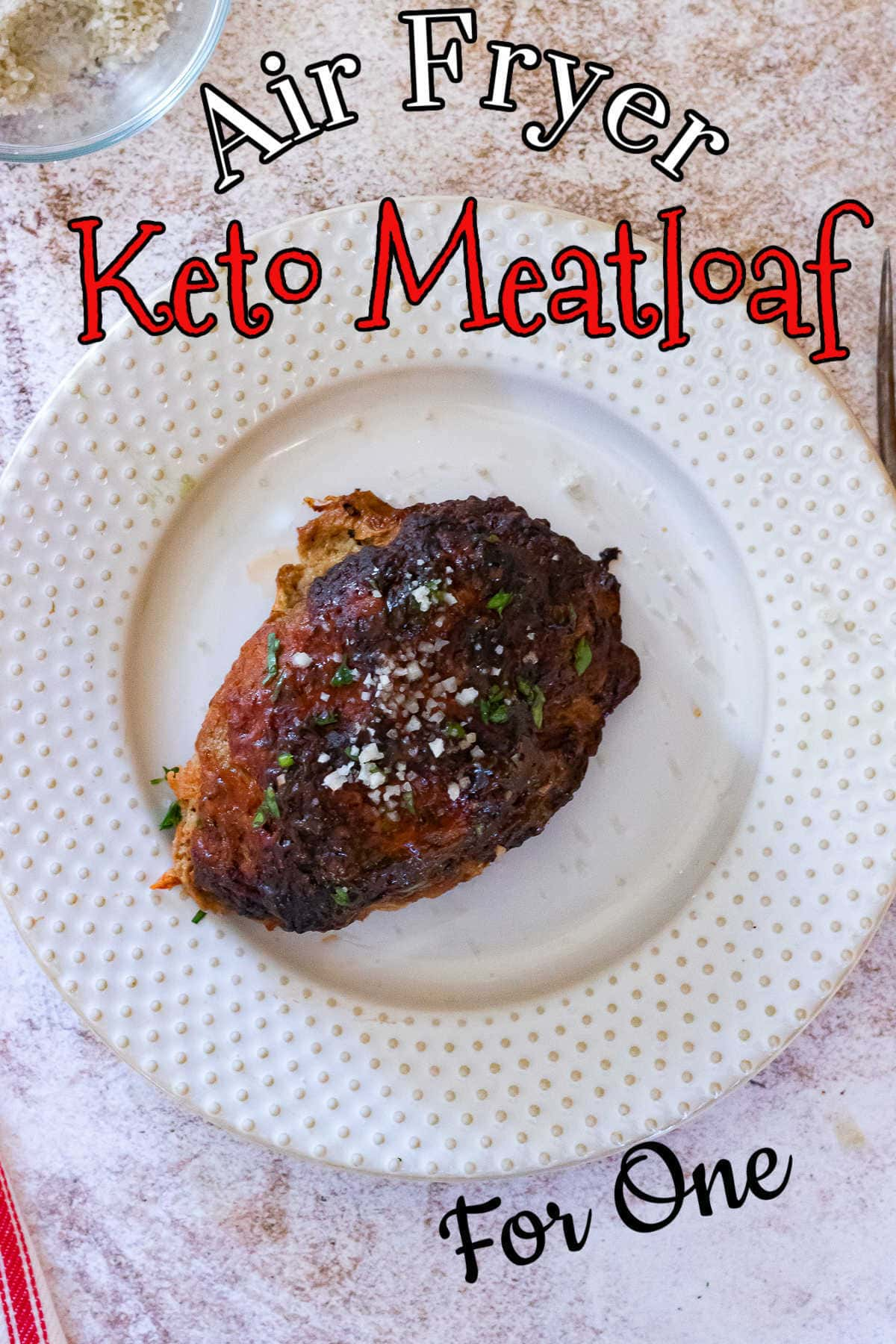 Serving of meatloaf on a white plate with the title text overlay.