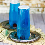 Two dark blue cocktails in champagne flutes.