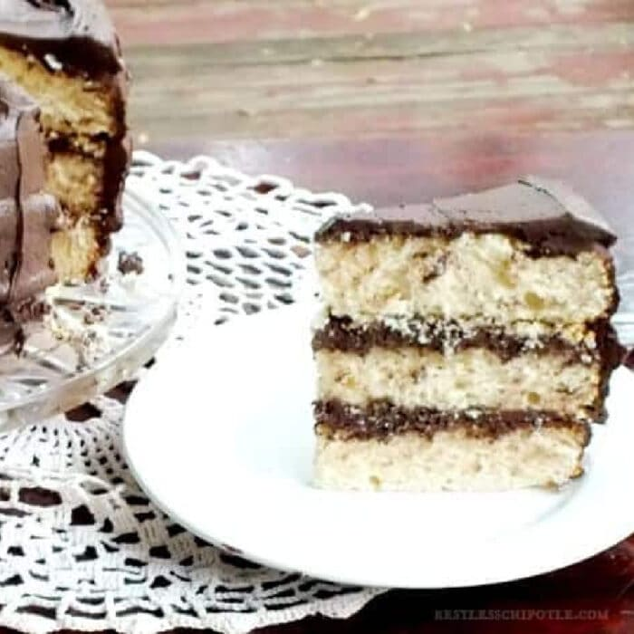 Slice of vanilla layer cake with chocoalte frosting.