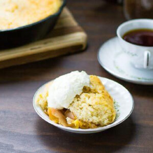 A bowl with a scoop of peach cobbler in it and ice cream on the top.