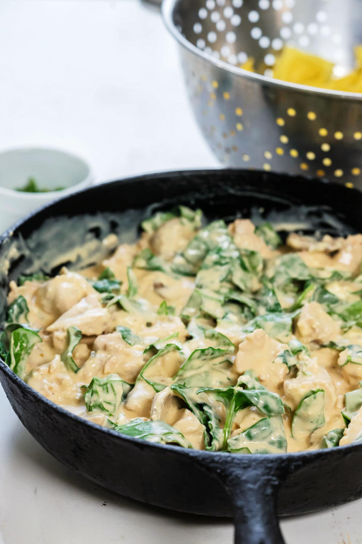 An iron skillet is full of the Alfredo chicken and spinach with cooked ravioli in a colander in the background.