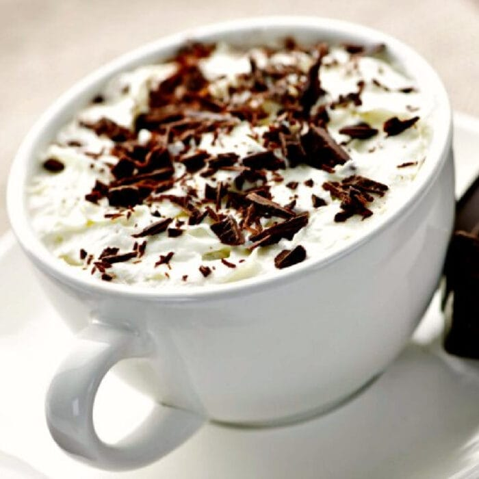 A cup of creamy Irish Coffee with chocolate on top.