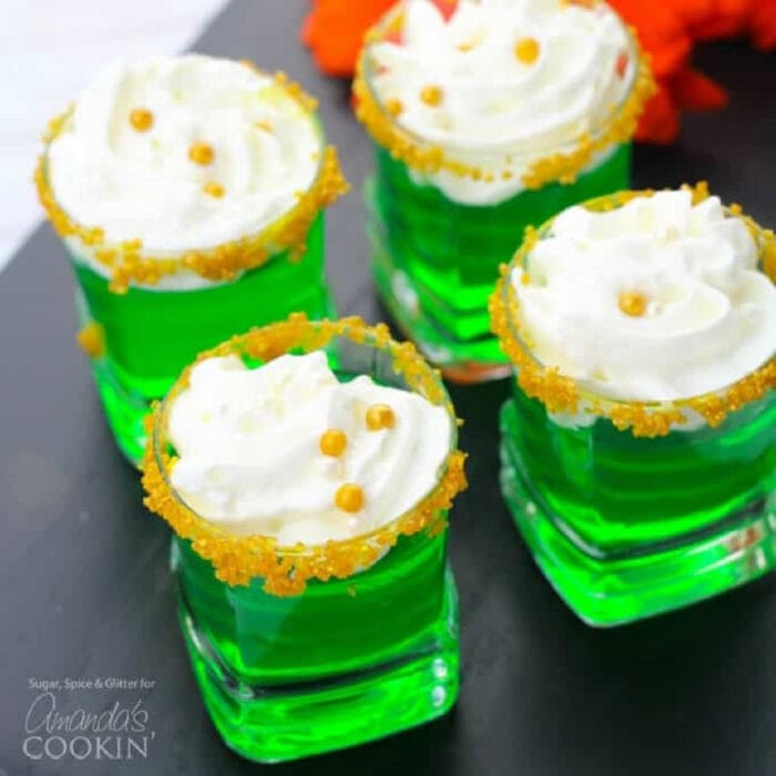 Four green jello shots with whipped cream on top in glasses garnished with gold sugar.