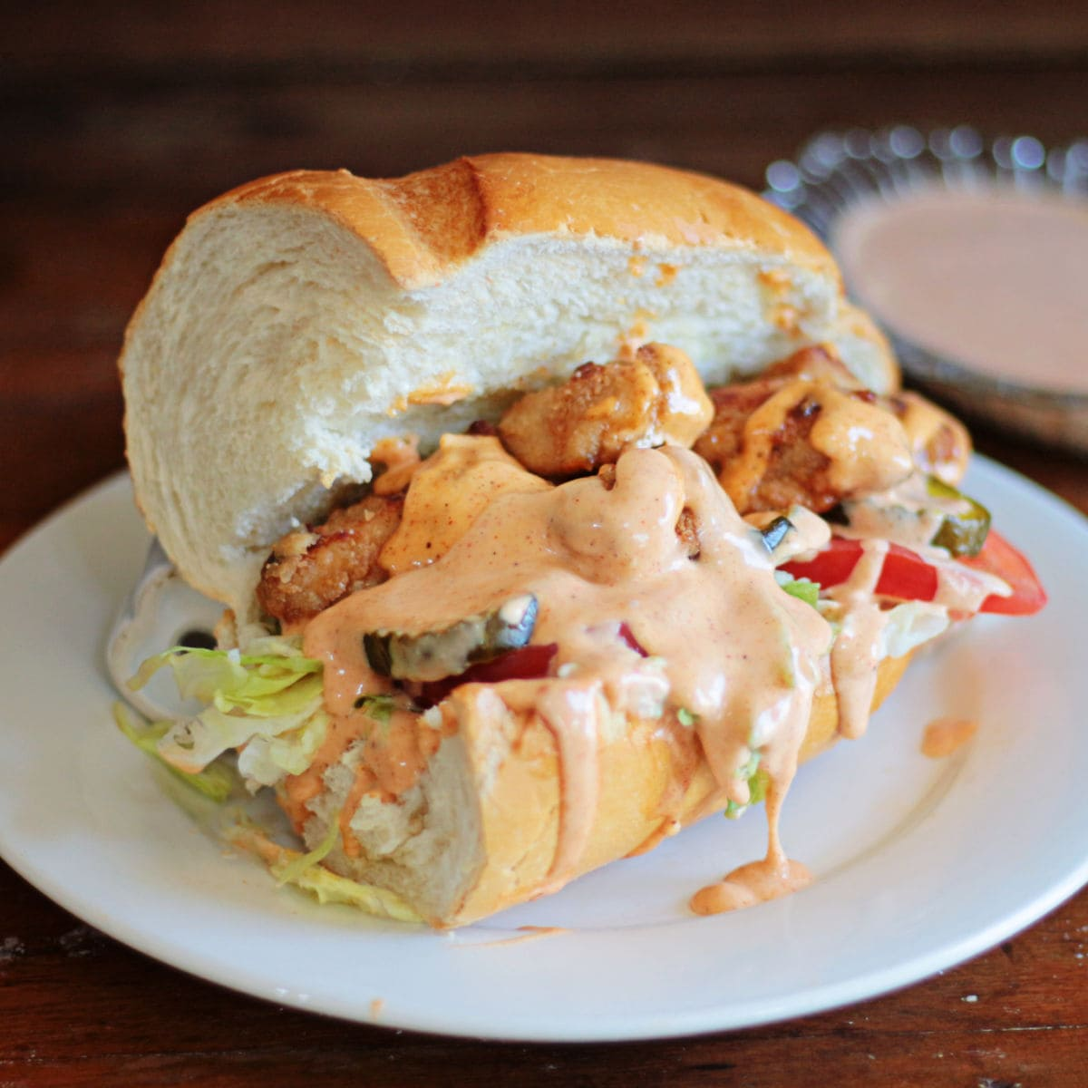 A  chicken po' boy sandwich dripping with spicy, homemade remoulade sauce.