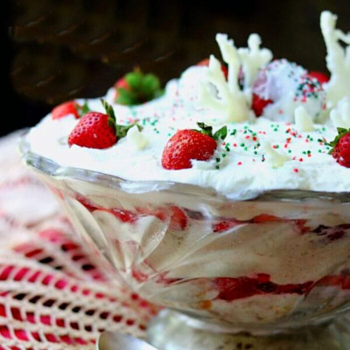 Layers of strawberries and cake in a punch bowl garnished with whipped cream on top.