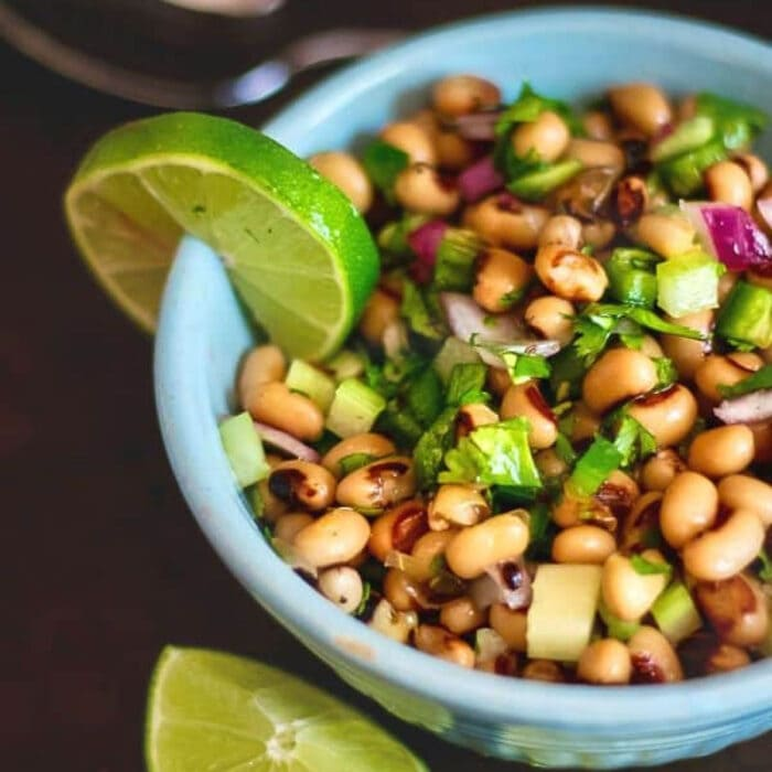 A bowl of. black-eyed peas shown from the top with a lime slice.