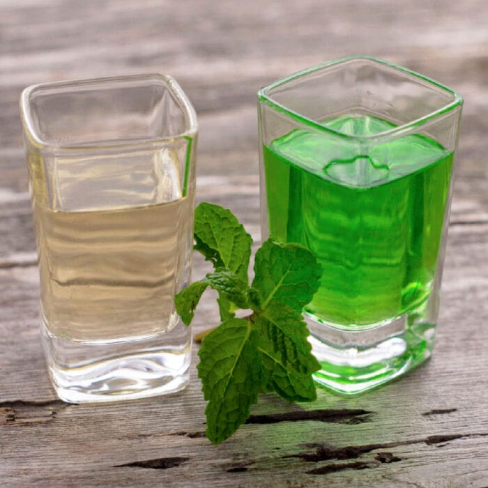 Green creme de menthe in one shot glass and clear in another.