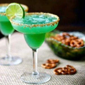 Green margarita in a glass with a gold rim and lime garnish.