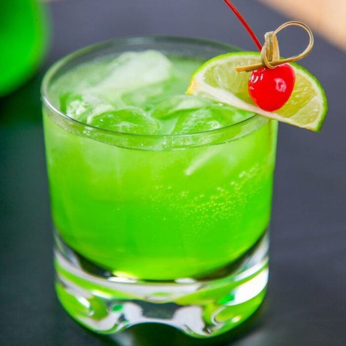 Green Midori Sour in an on the rocks glass garnished with a cherry.
