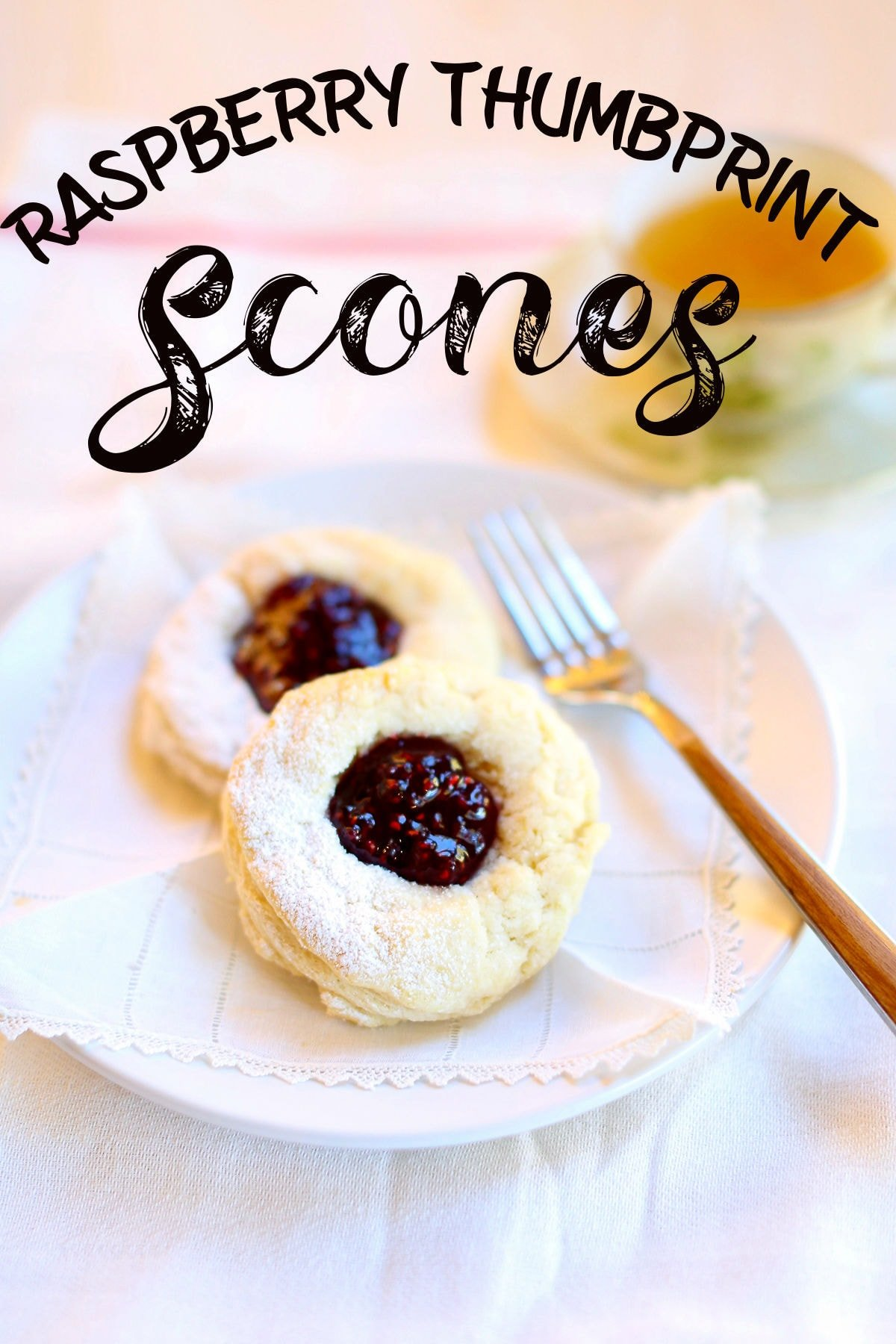 Two raspberry scones on a plate with a fork nearby.