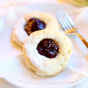 Close up of two raspberry thumbprint scones on a plate.