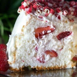 A slice of angel food cake filled with whipped cream and strawberries.