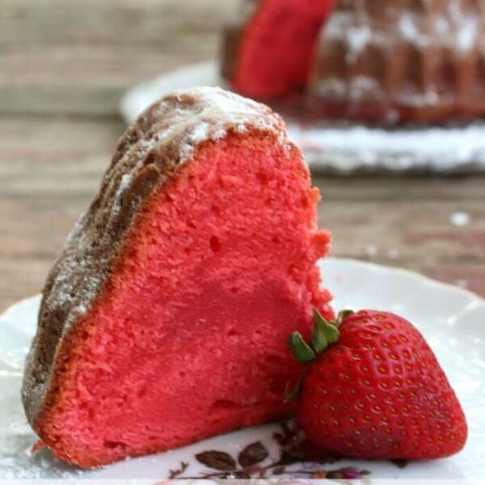 Close up of a slice of bright red strawberry pound cake.