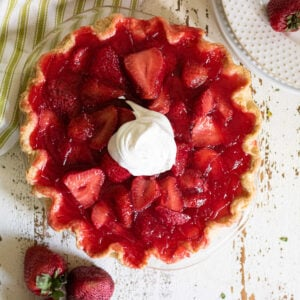 Overhead view of strawberry pie garnished with whipped cream.