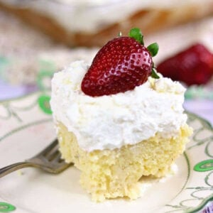 Square of yellow cake with a thick layer of cream on top.