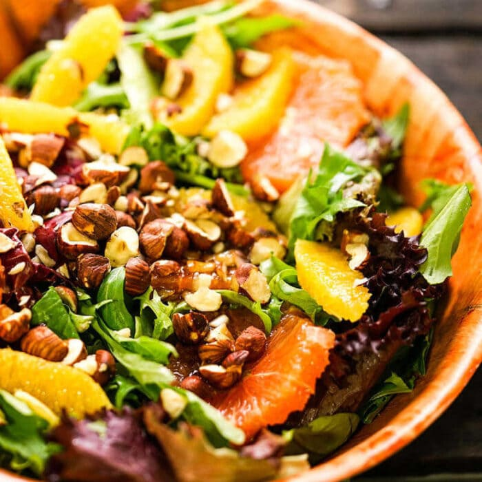 Citrus salad with greens in a wooden bowl.