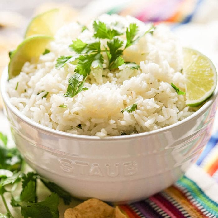A bowl of rice garnished with cilantro and lime.