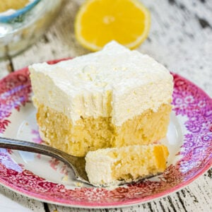 Closeup of a square of lemon cake showing the light texture of the frosting.