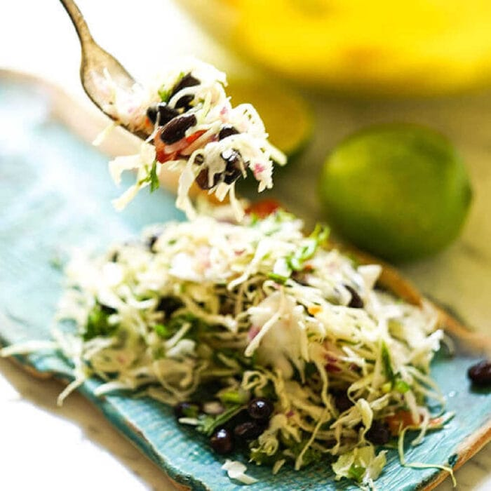 A forkful of Mexican coleslaw being lifted from a plate.