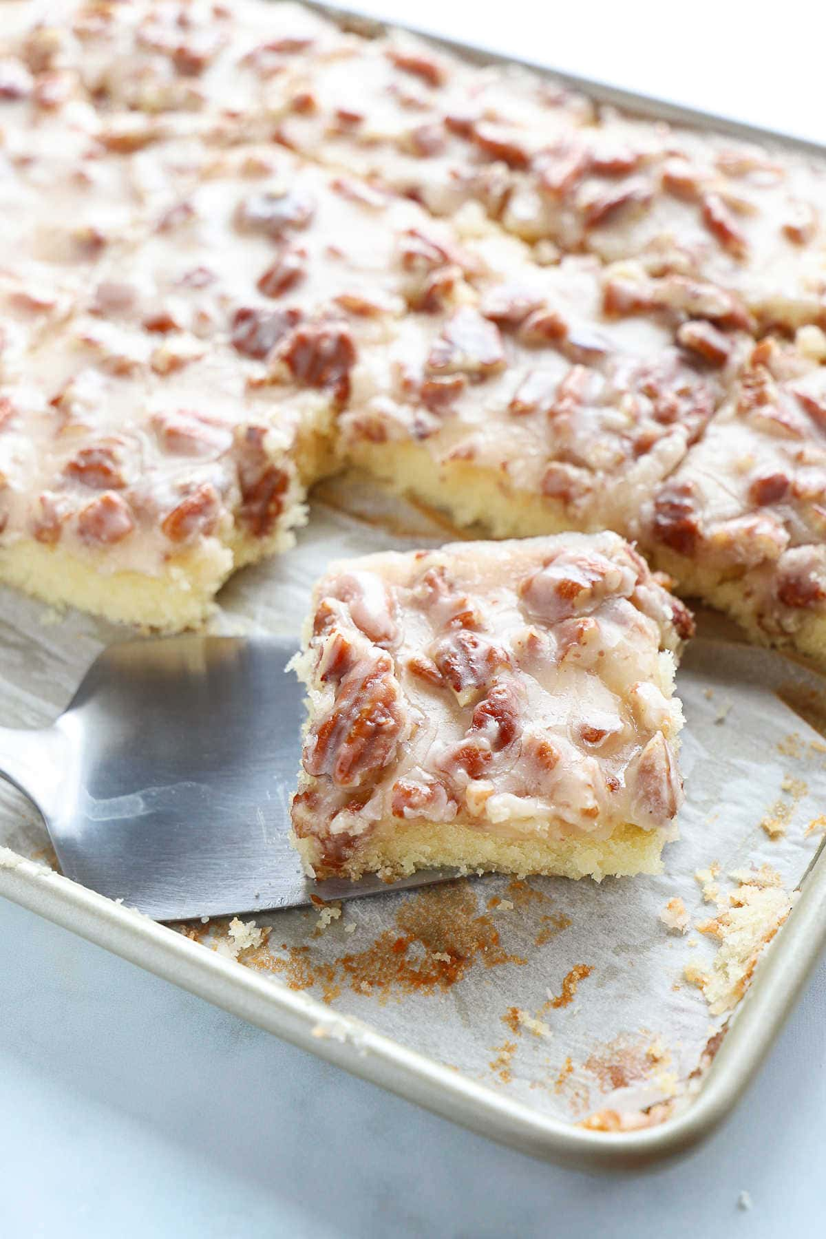 Vanilla sheet cake with a white fudge and pecan icing in a baking sheet.