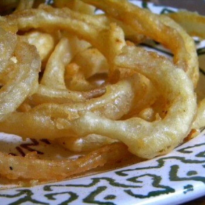 Crispy beer battered onion rings on a plate.