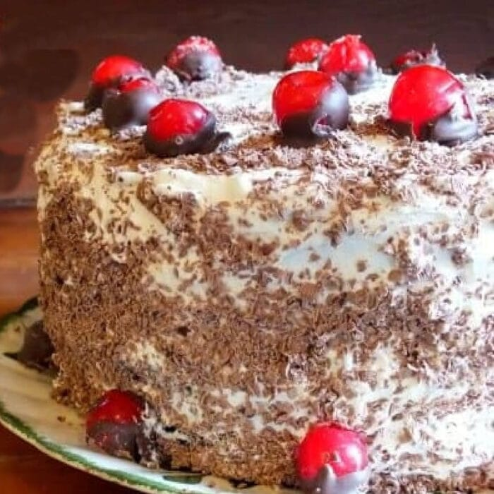 Black forest cake with chocolate covered cherries on it.