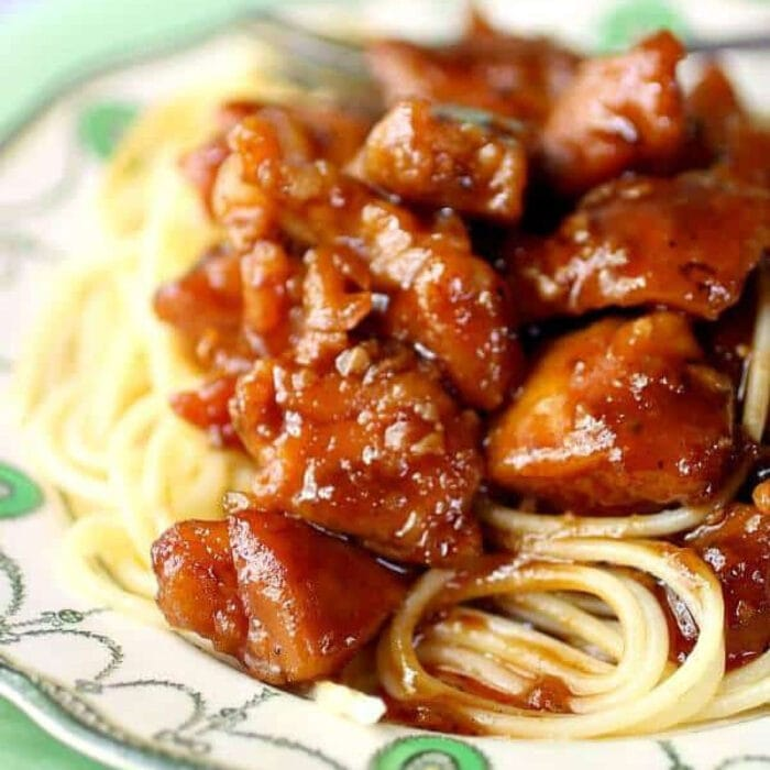 Cubes of chicken covered in a tangy sauce over spaghetti.