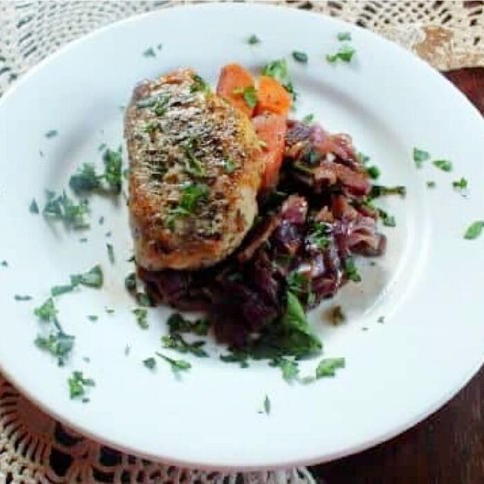 Golded brown braised pork and red cabbage on a white plate.