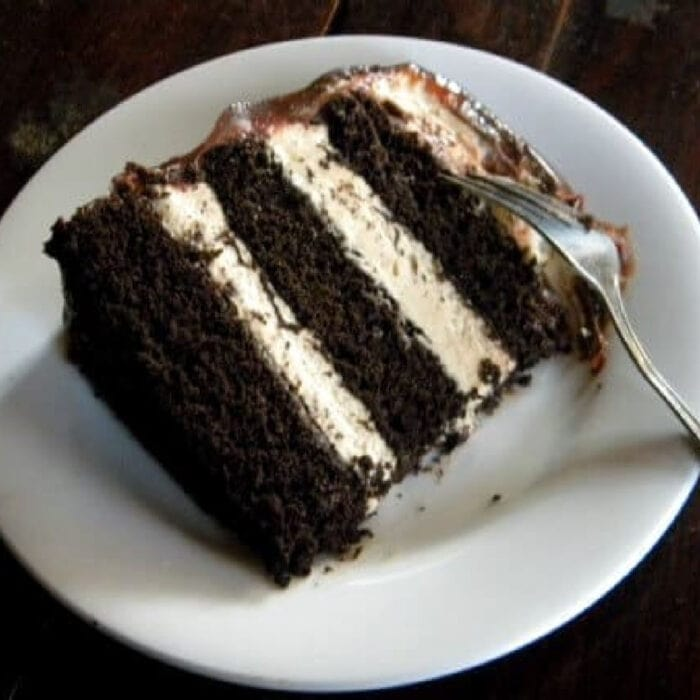 Slice of burnt sugar fudge layer cake with peanut butter mousse filling and frosting.