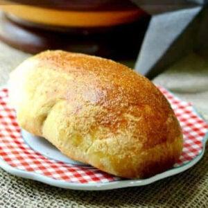 A golden brown cornmeal sandwich roll on a plate.